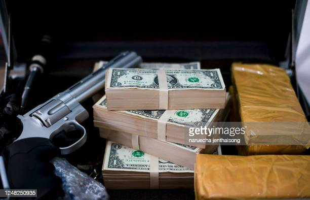 gun with bullets lying on the table. criminal problems. drugs and money on black background. illegal selling. - gang stock pictures, royalty-free photos & images