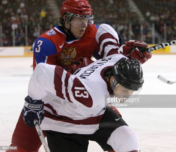 Gunars Skvorcovs of Latvia battles in the corner with Dmitri Kulikov of Russia at the Civic Centre on December 26, 2008 in Ottawa, Ontario, Canada.