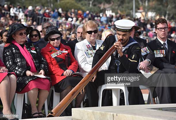 Gunggandji Able Seaman Alan Patterson of NUSHIP Adelaide plays the didgeridoo before the national service commemorating the centenary of the...