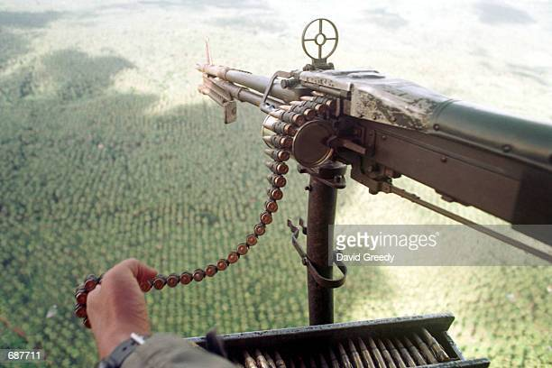 A gunman aboard a Huey helicopter watches for movement December 15 2001 in the heavily forested area believed to be where the Abu Sayyaf Group is...