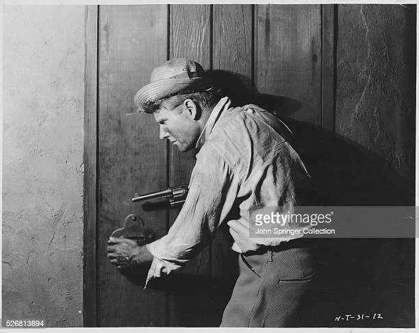 Gunman cautiously starts to open a door in a scene from the 1923 film The Song of Love.