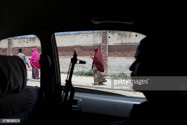 A gunman looks from a car window in Mogadishu towards a woman wearing a veil