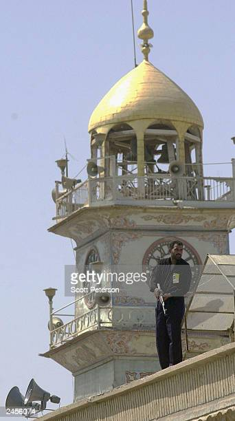 Gunman watches over the crowd from the roof of the Imam Ali shrine as the cortege of Iraq's most powerful Shiite leader Ayatollah Mohamed Bakr...