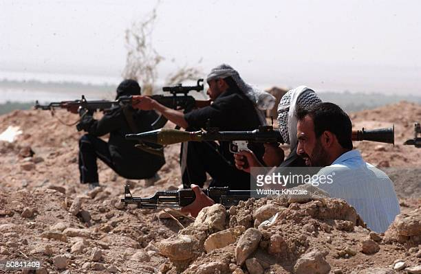 Gunmen loyal to radical cleric Moqtada al-Sadr take up an ambush position May 15, 2004 near the cemetery of the holy city of Najaf, Iraq. U.S forces...