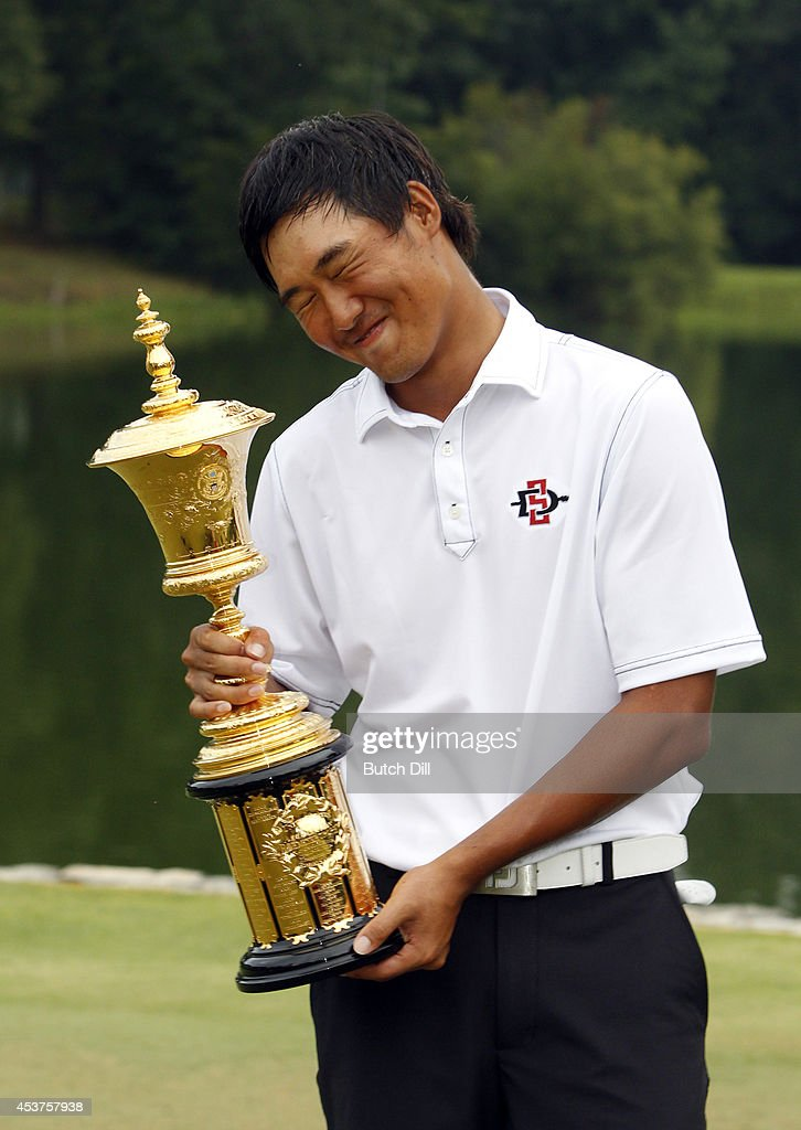 Gunn Yang of Korea, kisses the trophy after defeating Corey Conners of Canada, to win the U.S. Amateur Championship 2-1 on the seventeenth hole on August 17, 2014 at the Atlanta Athletic Club in Johns Creek, Georgia.