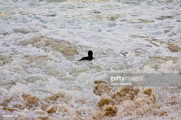A lone swimmer battles turbulent currents and a treacherous sea.