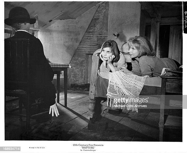 Gunnel Lindblom and Patricia Gozzi laying on a bed while looking at the scarecrow in the room in a scene from the film 'Rapture' 1965