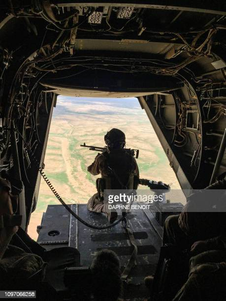 A gunner mans a machine gun at the back of a US Marine Corps V22 Osprey flying near a French artillery forward operating base near alQaim in Iraq's...