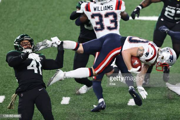 Gunner Olszewski of the New England Patriots carries the ball and trips over Matthias Farley of the New York Jets during the first half at MetLife...
