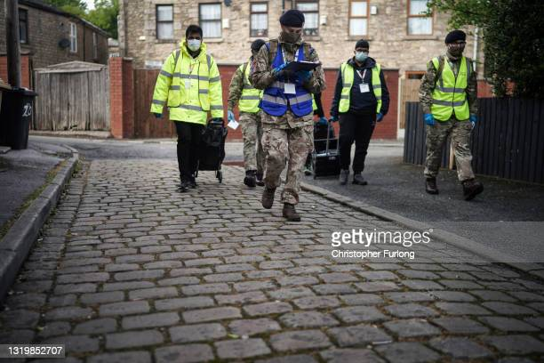 Gunners from the Royal Horse Artillery and Bolton council workers distribute Covid-19 polymerase chain reaction tests to local residents on May 24,...