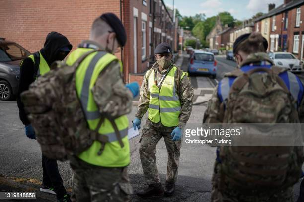 Gunners from the Royal Horse Artillery distribute Covid-19 polymerase chain reaction tests to local residents on May 24, 2021 in Bolton, England. The...