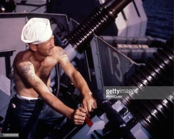 Gunner's Mate Second Class Charles J Hansen works on 40mm quad antiaircraft gun mount during the shakedown cruise of the Iowaclass battleship USS...