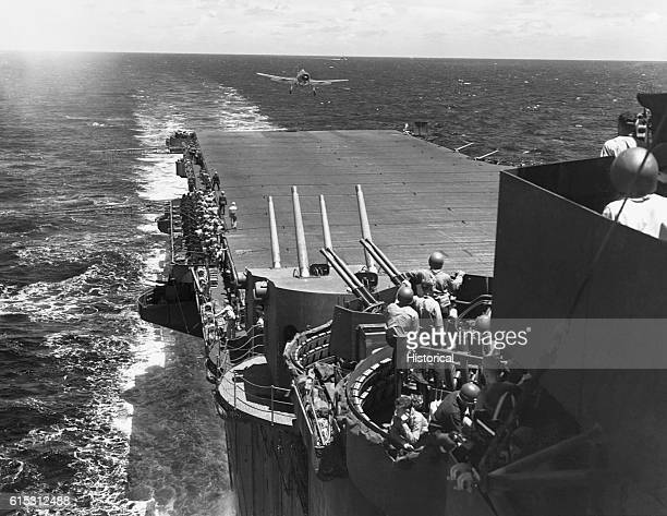 Guns manned and ready as a F6F fighter aircraft lands on the flight deck of the USS Lexington during the Japanese air attack on task force 58 in the...