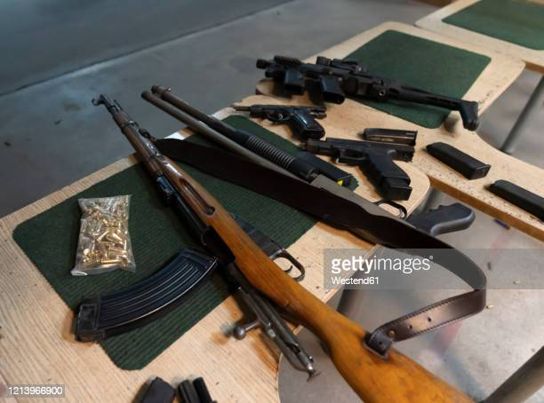 guns on the table in shooting range - weapon stock pictures, royalty-free photos & images
