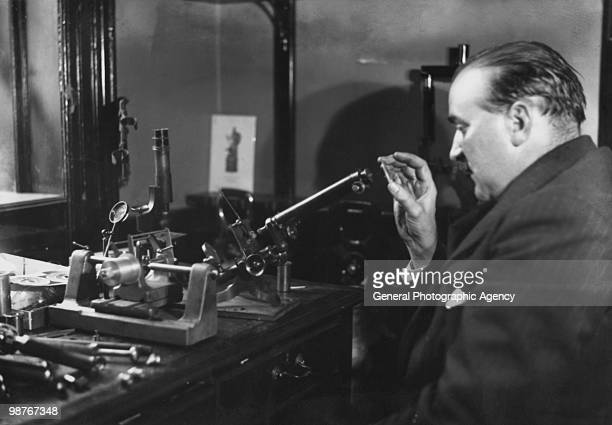 Gunsmith and ballistics expert Robert Churchill using a microscope to help compile a ballistic report for Scotland Yard in the case of the murder of...