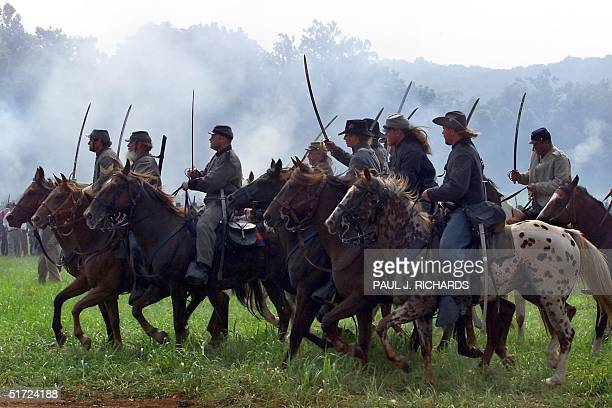 Gunsmoke fill the air as Cavalry soldiers charge the battlefield with sabres at the First Manassas Civil War Reenactment 04 August 2001 in Leesburg...