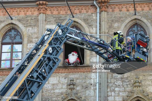 Gunter Grobe, dressed as Santa Claus, opens the 16th windows while children are taken up to him on a turnable ladder by the fire brigade at the city...