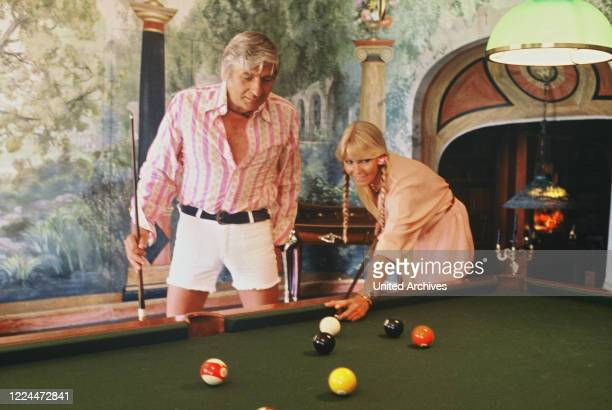 Gunter Sachs is playing pool billiard with wife Mirja 1970s