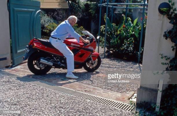 Gunter Sachs on a Kawaski motor bike