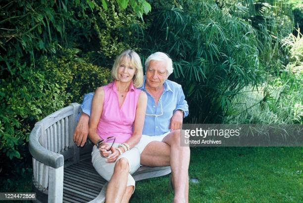 Gunter Sachs with wife Mirja sitting in the garden together on a bench 2000s