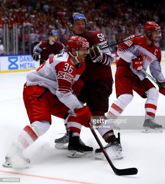 Guntis Galvins of Latvia and Jannik Hansen of Denmark battle for the puck during the 2018 IIHF Ice Hockey World Championship Group B game between...