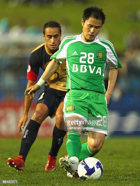 Guo Hui of Guoan dribbles the ball ahead of Tarek Elrich of the Jets during the AFC Champions League Group match between the Newcastle Jets and the...