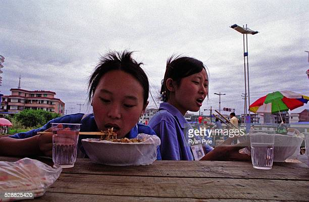Guo Jing and Wei Wen Qing enjoy their lunch at a small noodle shop across the street from their textile factory in YiWu On January 1 2005 textile...