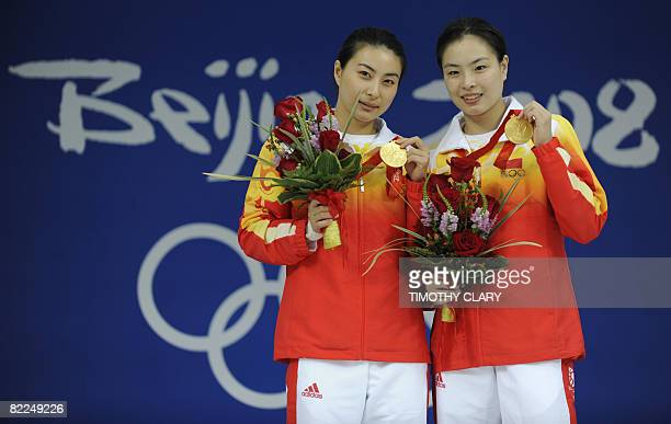 Guo Jingjing and Wu Minxia hold their gold medals during the medal ceremony for the women's 3 meter springboard synchronised diving final at the...