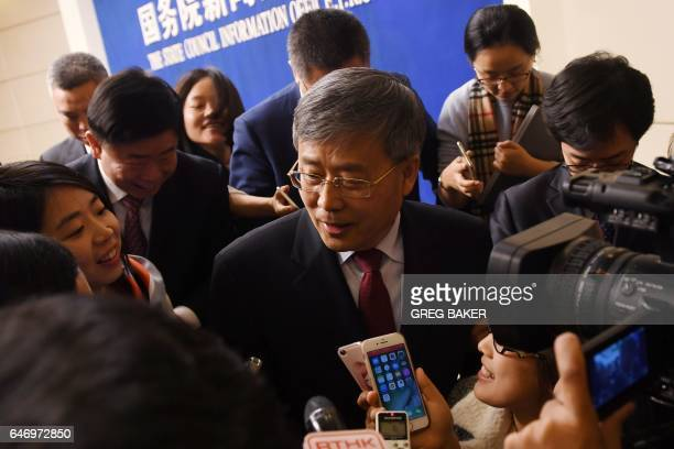 Guo Shuqing Chairman of the China Banking Regulatory Commission speaks to journalists as he leaves a press conference in Beijing on March 2 2017 /...