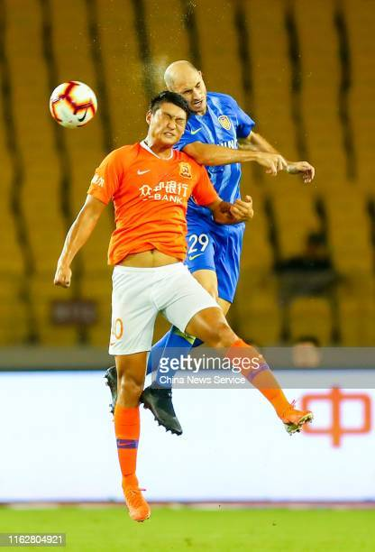 Guo Tianyu of Wuhan Zall and Gabriel Paletta of Jiangsu Suning vie for the ball during the 2019 Chinese Football Association Super League 18th round...