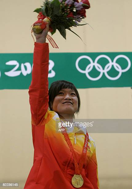 Guo Wenjun of China celebrates on the podium after winning the gold medal in the women's 10m Air Pistol category at the 2008 Beijing Olympic Games on...