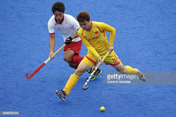 Guo Xiaoping of China shields the ball from Ryohei Kawakami of Japan in the men's classification 56 placing on day thirteen of the 2014 Asian Games...
