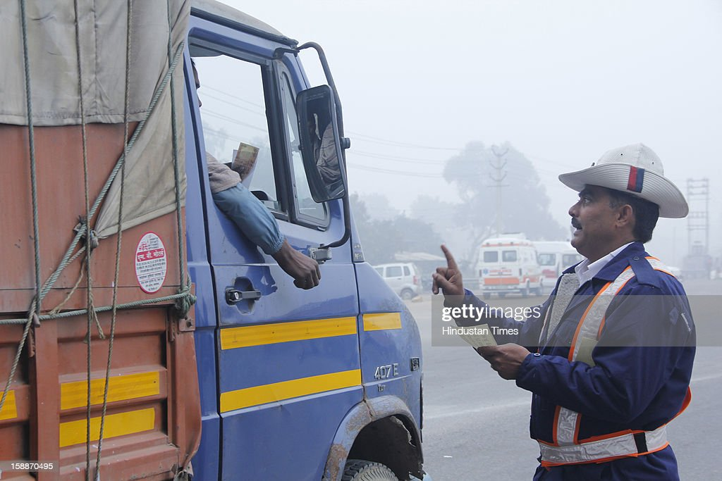 Gurgaon police distribute pamphlet at Kherki Daula toll plaza during road safety week on January 2, 2013 in Gurgaon, India.