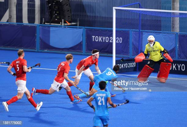 Gurjant Singh of Team India scores their team's second goal past Oliver Payne of Team Great Britain during the Men's Quarterfinal match between India...