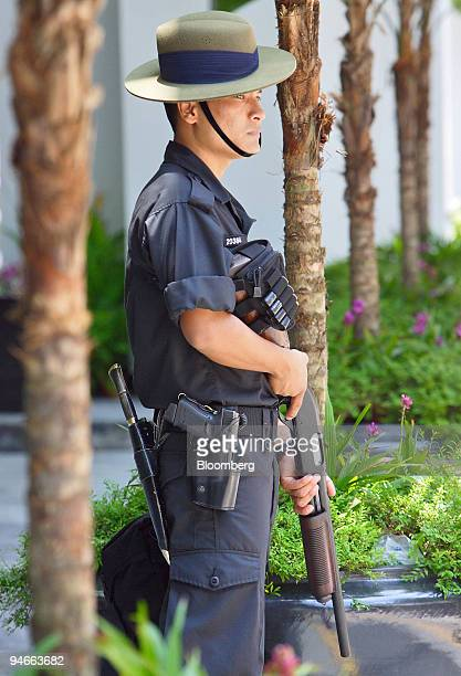 Gurkha keeps his finger near the trigger of his shotgun as he stands guard outside the Suntec convention center venue for the International Monetary...