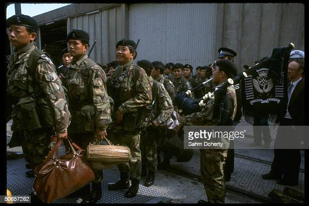 Gurkha Rifles troops including bagpipe player boarding QE2 before sailing to Falklands
