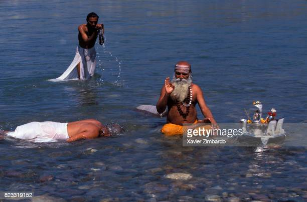 A guru gives blessings sitting in the Ganges while pilgrims are praying around him with signs of their devotion for the water of the holy river...