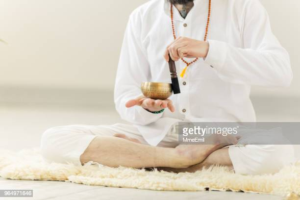 guru practicing kundalini yoga and meditation with a singing bowl - yogi stock photos and pictures