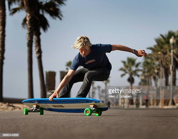 Gus Hamborg does a tail slide a move that complements his surfing style on a 6'8' long Hamboard longboard skateboard along the Huntington Beach bike...