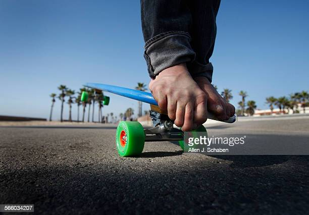 Gus Hamborg hangs ten a move that complements his surfing style on a 6'8' long Hamboard longboard skateboard along the Huntington Beach bike path...