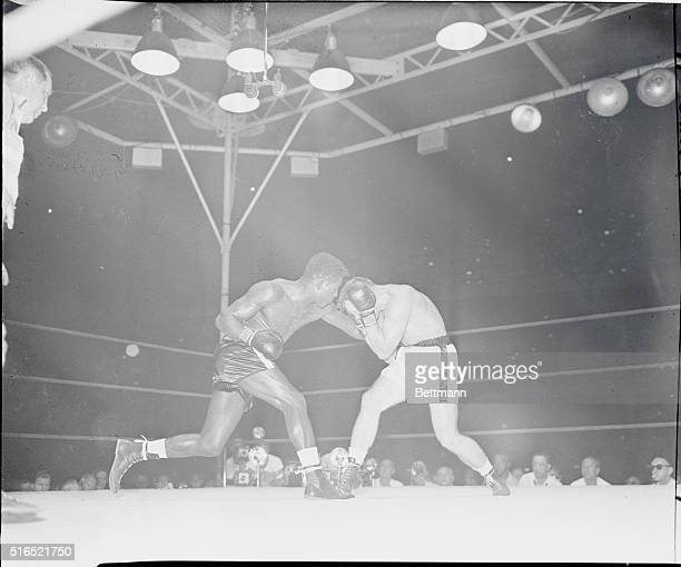 Gus Lesnevich receives a stomach punch from Ezzard Charles in the late rounds of a fight in August 1949