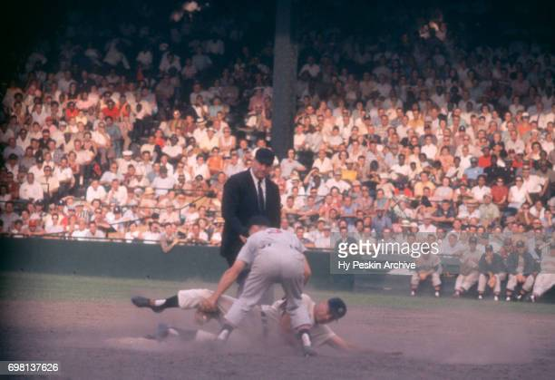 Gus Zernial of the Detroit Tigers is caught stealing as he is tagged out by Woodie Held of the Cleveland Indians as umpire Hank Soar is there to make...