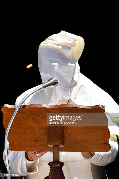 A gust of wind blows Pope Francis' cape as he delivers his speech after a meeting with religious leaders at the Pontifical Basilica of St Nicholas in...