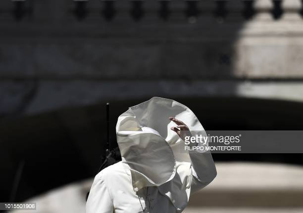 A gust of wind blows the mantle of Pope Francis as he blesses the faithfuls after a mass to the italian youths at St Peter's square in the Vatican on...