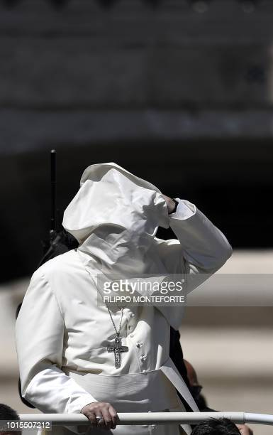 A gust of wind blows the mantle of Pope Francis prior his Angelus prayer at St Peter's square in the Vatican on August 12 2018
