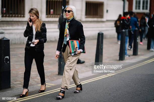 A gust wears a colored striped clutch a black jacket camel pants outside Preen by Thornton Bregazzi during London Fashion Week September 2017 on...