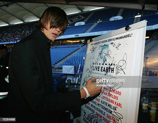 Gustaf Noren of the Swedish rock band Mando Diao signs on a poster during the Hamburg Live Earth concert at the HSH Nordbank Arena on July 7 2007 in...