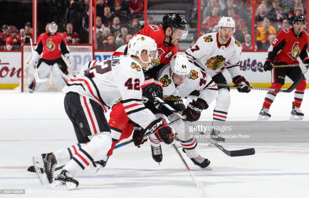 Gustav Forsling #42 and Jan Rutta #44 of the Chicago Blackhawks defend against a puck carrying Mark Stone #61 of the Ottawa Senators in the second period at Canadian Tire Centre on January 9, 2018 in Ottawa, Ontario, Canada.