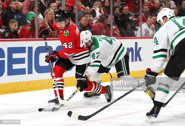 Gustav Forsling of the Chicago Blackhawks and Alexander Radulov of the Dallas Stars chase the puck in the first period at the United Center on...