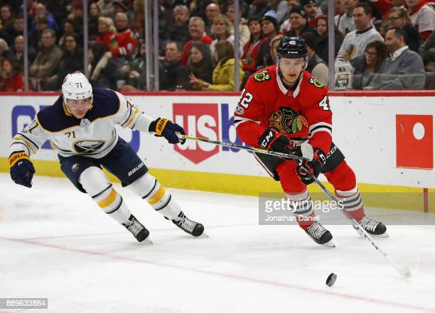 Gustav Forsling of the Chicago Blackhawks and Evan Rodrigues of the Buffalo Sabres move to the puck at the United Center on December 8 2017 in...